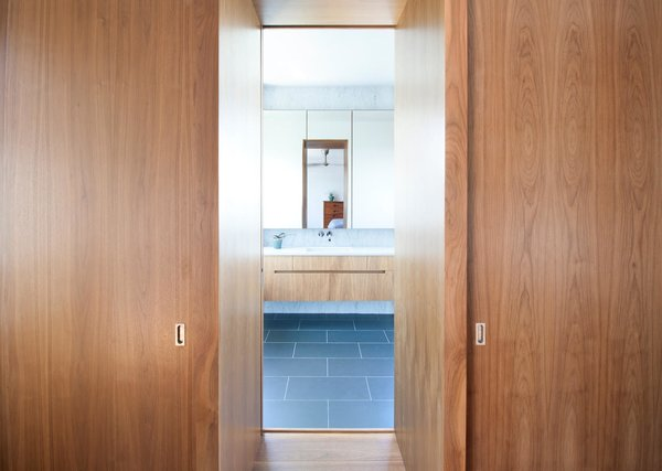 A view from from the bedroom to the ensuite bath. Custom walnut millwork brings warmth and cohesion to the master retreat.