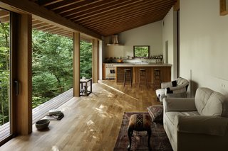 Materials for the interior were chosen to foster a relaxed vacation home atmosphere. Teak floors and pine beams create a warmth and easiness in the main living space, while helping to establish a natural dialogue with the forested landscape.
