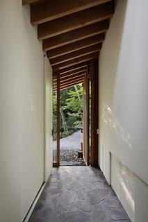 温馨入口走廊设有天然石材浅间和松树天花板横梁,带隐藏式储物空间一起。推拉壁柜门纳入从网站上发现倒下的树枝制成的门把手。