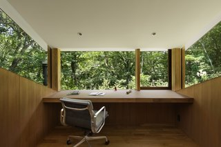 An inspiring place to work or read, the cozy home office features teak flooring, desk, and wall paneling. The warmth and simplicity of the interior allows nature—even the tiniest of life forms—to come into full focus.