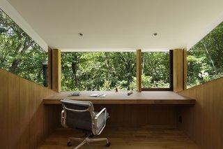 一个鼓舞人心的工作或阅读的地方,舒适的家庭办公室特点柚木地板,办公桌和墙壁镶板。室内的温暖和简单让自然——即使是最微小的生命形式——得到充分的关注。