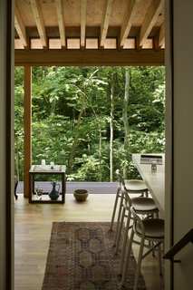 "Cozy interiors with simple finishes allow the focus to remain steadily on the verdant natural surroundings. ""The house is located in the middle of an overwhelming forest, so we [put the] focus on nature...and the wildflowers on the roof,"" explains Nakamura."