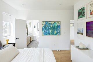 """The main bedroom features a calming, muted palette, punctuated by vibrant pops of color. The decision to prioritize this particular space came after years of living in tighter quarters. """"We went bigger where it needed to be with the primary bedroom and bath, a need after years of living in studios and one-bedroom apartments,"""" explains Todd."""