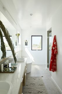 """The main bathroom, with a prominently placed soaking tub, is a restorative haven within the home. """"My favorite part [of the home] is the bathtub, which has a clerestory window of the downtown skyline, and another window that looks out to see the Hollywood sign in the distance,"""" shares Melanie. The luminous space features ceramic floor tile from Ceramic Technics in Ecco Mineral Stone 2.0, Wilsonart quartz counters in Rio Upano, and a white LED sconce by StudioM. The white oak vanity was custom designed by OPEN For Humans."""