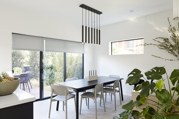 The semi-enclosed dining room enjoys a fluid connection to the back deck for breezy indoor/outdoor living. A Lineaire Blackened Bronze 7 Bulb Pendant from CB2 hangs above a Muuto Adaptable Table with HAY Soft Edge 12 Side Chairs.