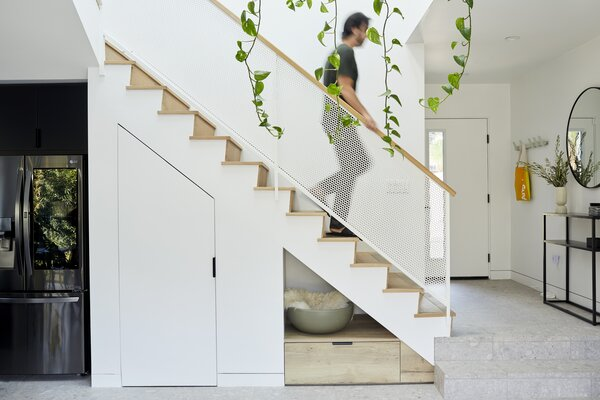 """With the home's relatively compact footprint and efficient floor plan comprising two bedrooms and two bathrooms over a single living level, smart use of space was critical. """"Built-in storage everywhere [is] number one,"""" says Melanie. A pantry and storage drawers are tucked under the stairs."""