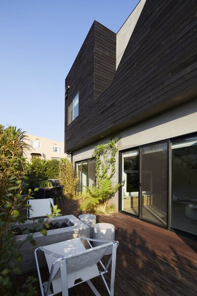 """Protected with landscaping, the cozy ipe deck and fire pit is an inviting space Melanie and Todd frequently find themselves gravitating toward. """"It essentially acts as an extension of our living room,"""" says Todd."""