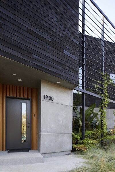 Both privacy screen and modern trellis, the slatted steel frame continues the angled geometry of the facade, extending the plane of the entrance and carport to the corner of the home. Concrete and clear-coated cedar slats complete the facade, and aluminum Ridge house numbers by Hsiaolin Chi for NakNak adorn the home's entrance.