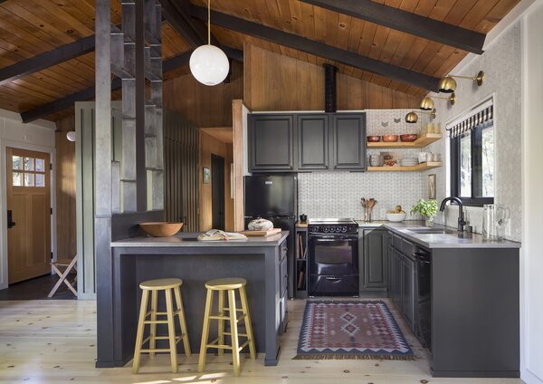 The spectacular kitchen renovation includes repurposed cabinets, almost entirely unrecognizable after their modern facelift. The original cabinets were painted (Benjamin Moore 'Onyx') and reinstalled in an updated configuration. Even the new kitchen peninsula was made from reused original cabinets.