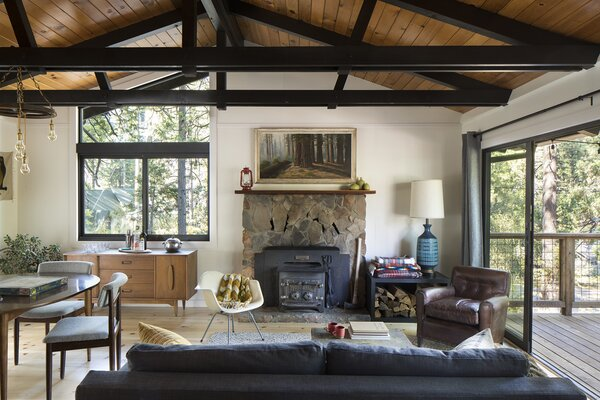 A new trapezoid window follows the angle of the roof, and large new sliding doors connect to the deck, allowing the once dark and cramped living room to feel open and inviting.