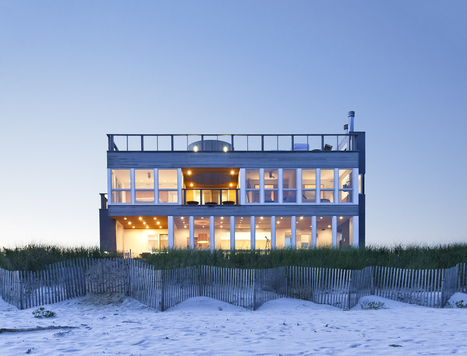 House Building Type, Wood Siding Material, Metal Siding Material, Grass, Wood Fences, Wall, Vertical Fences, Wall, Horizontal Fences, Wall, and Bedroom South elevation at dusk  Dune Road Beach House by Resolution: 4 Architecture
