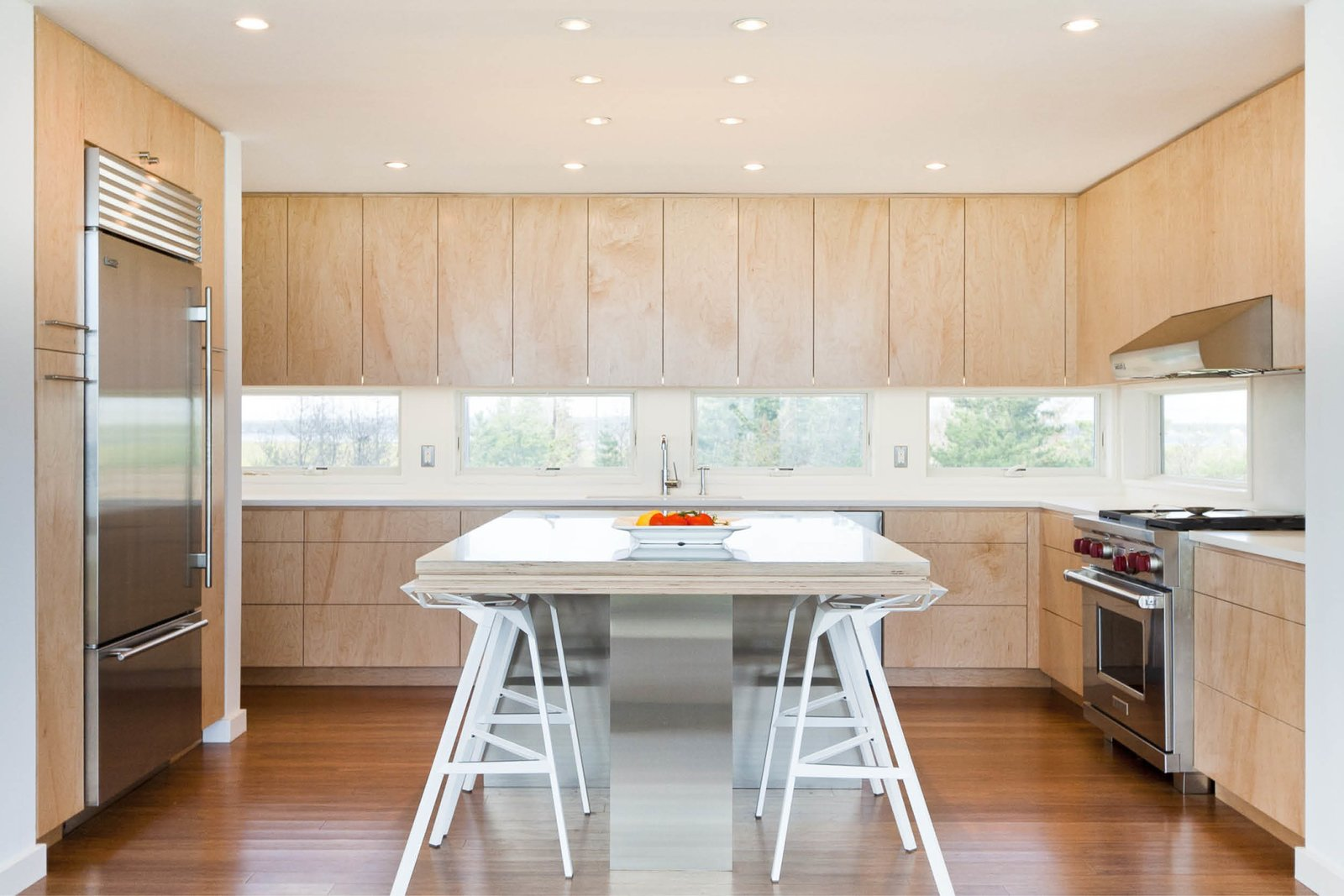 Medium Hardwood Floor, Ceiling Lighting, Range Hood, Engineered Quartz Counter, Refrigerator, Wall Oven, Cooktops, Drop In Sink, Wood Cabinet, Stools, and Dining Room Kitchen cabinets and horizontal slot windows frame views of the bay to the north  Dune Road Beach House by Resolution: 4 Architecture