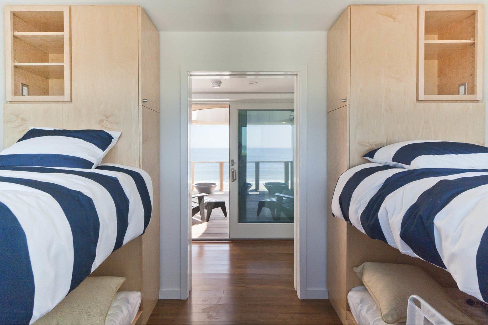 Bed, Storage, Bunks, Wardrobe, Medium Hardwood Floor, Kids Room, and Bedroom Room Type Bunk room with oculus deck and ocean beyond  Dune Road Beach House by Resolution: 4 Architecture