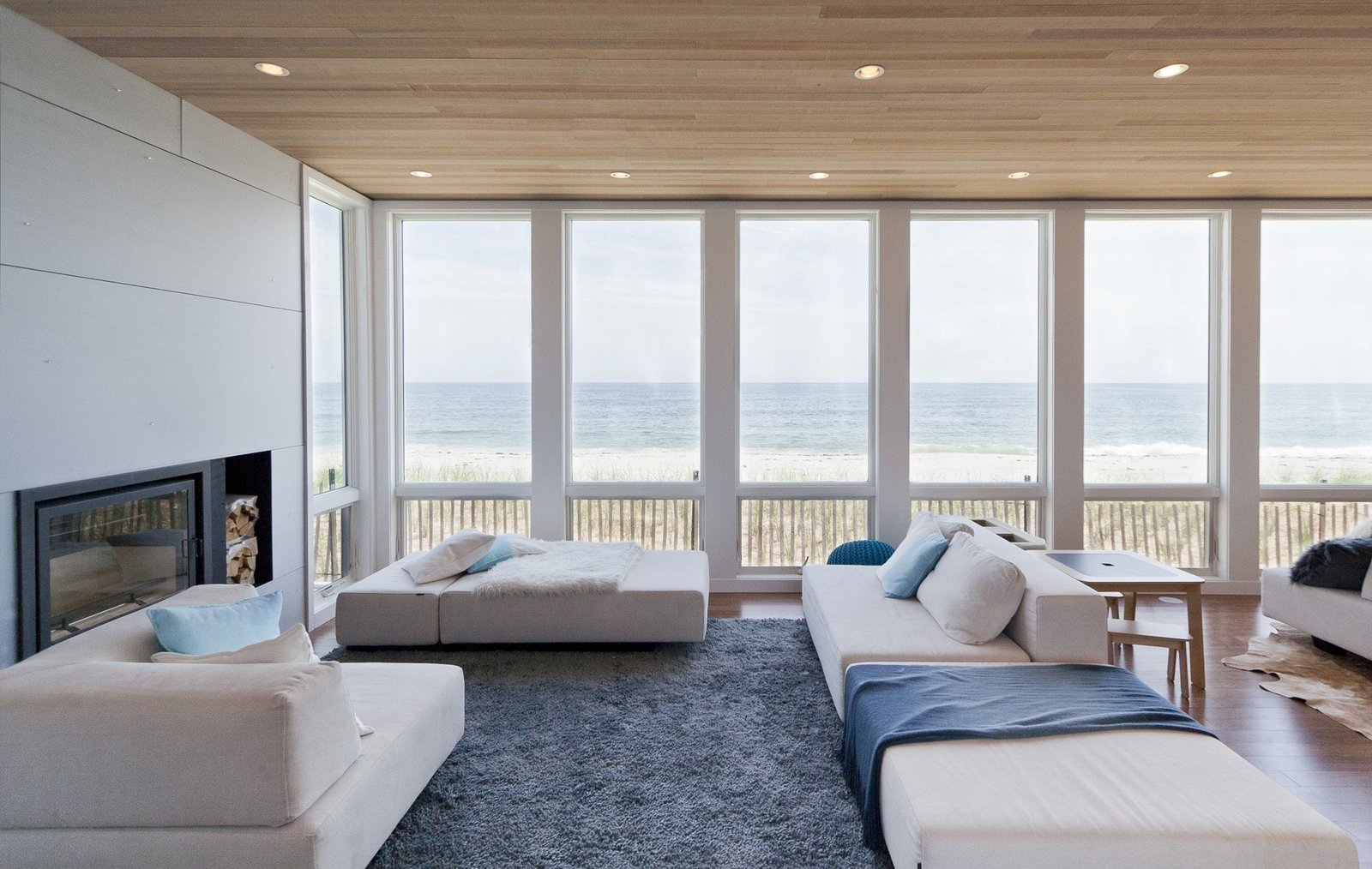 Medium Hardwood Floor, Wood Burning Fireplace, Ceiling Lighting, Sofa, and Living Room Living room and view of Atlantic Ocean upon entry  Dune Road Beach House by Resolution: 4 Architecture