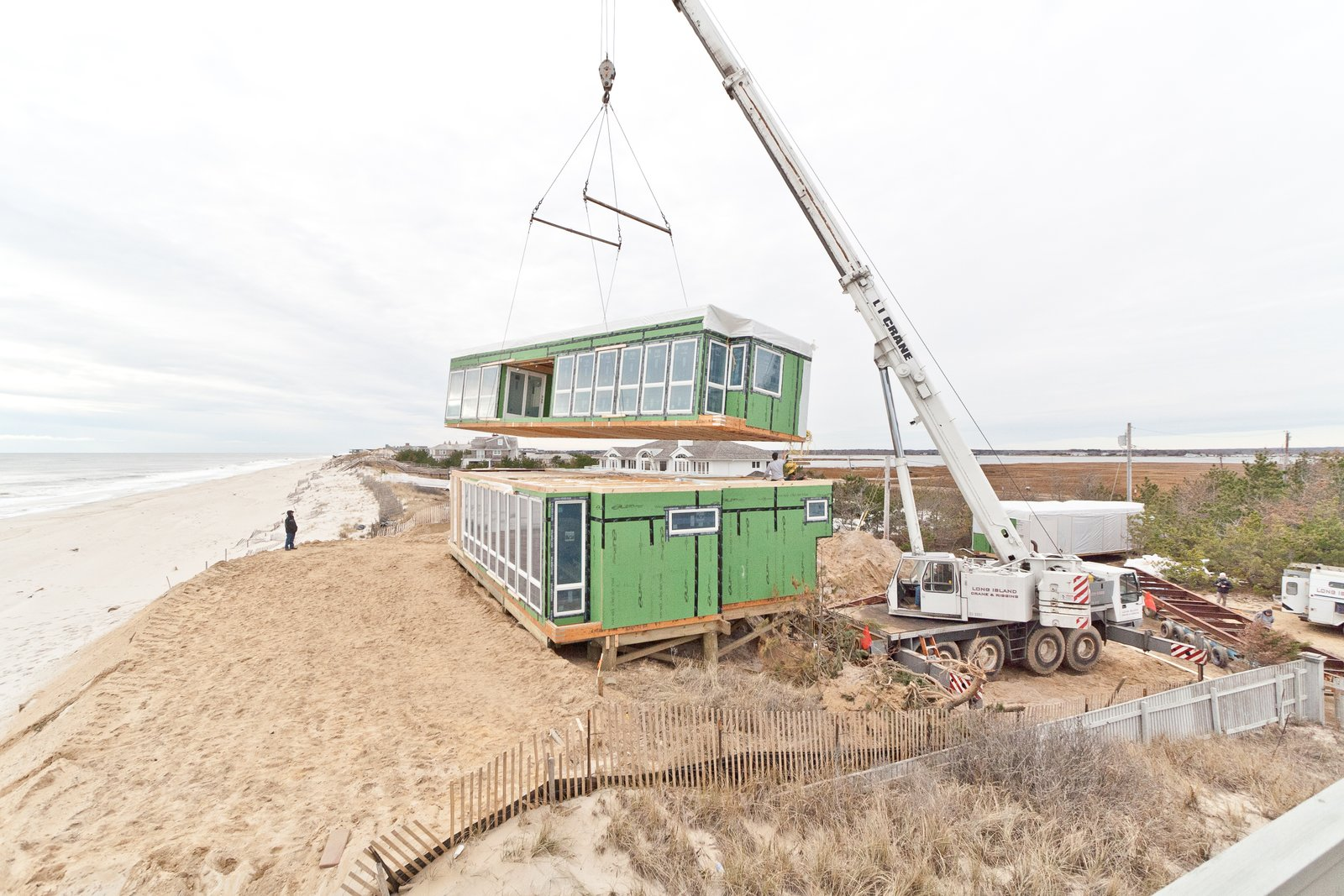 Second-floor module being set as seen from neighboring house  Dune Road Beach House by Resolution: 4 Architecture