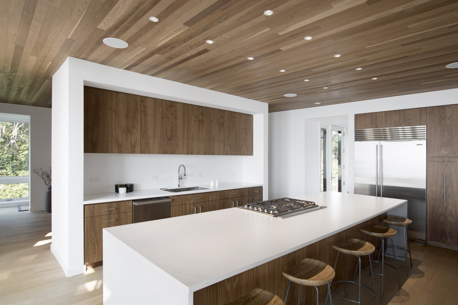 Kitchen, Ceiling Lighting, Refrigerator, Cooktops, Dishwasher, Engineered Quartz Counter, Light Hardwood Floor, Drop In Sink, and Wood Cabinet Kitchen  North Fork Bluff House by Resolution: 4 Architecture