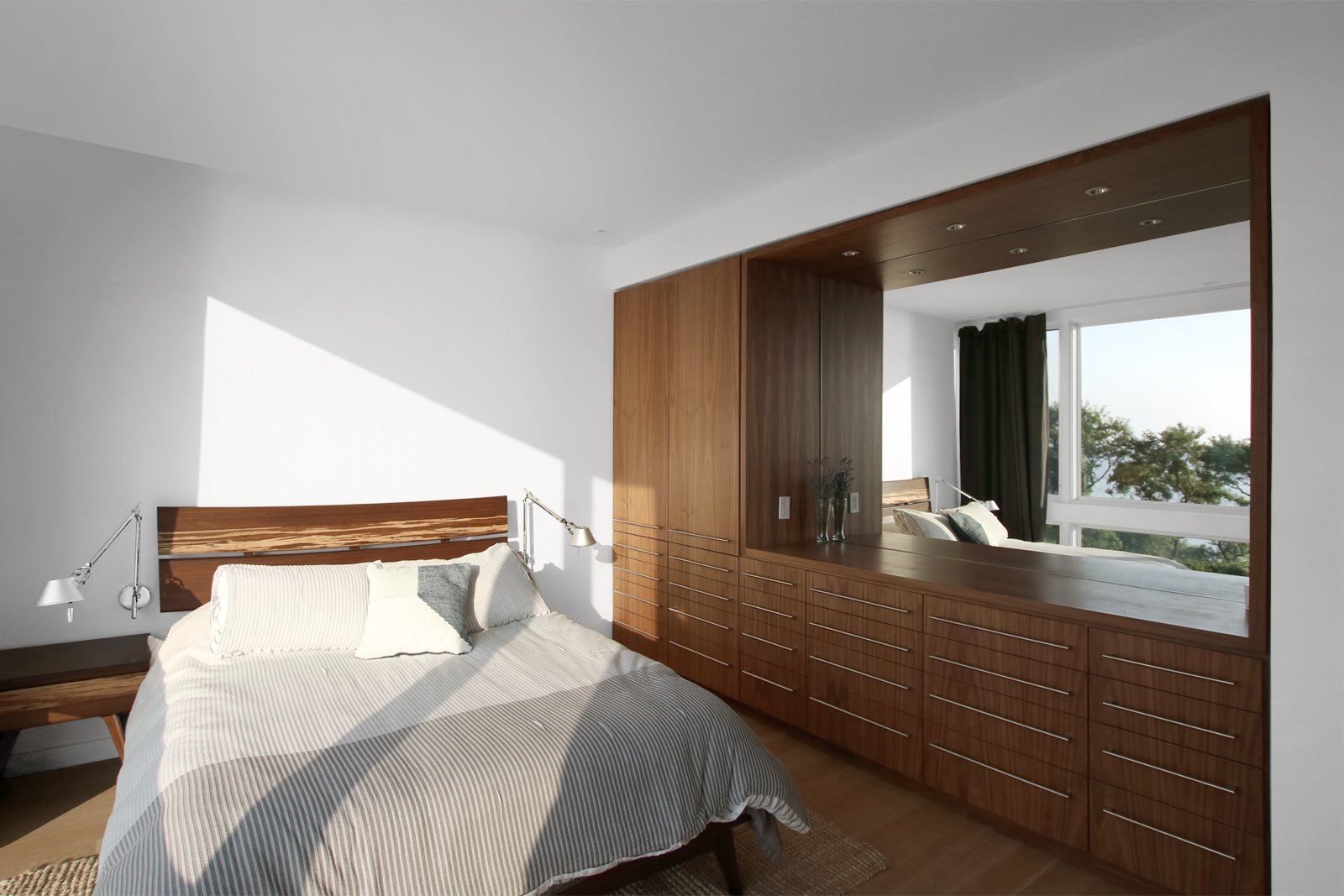Bedroom, Light Hardwood Floor, Wardrobe, Ceiling Lighting, Bed, Dresser, and Night Stands Bedroom at rear of home with view to Long Island Sound  North Fork Bluff House by Resolution: 4 Architecture