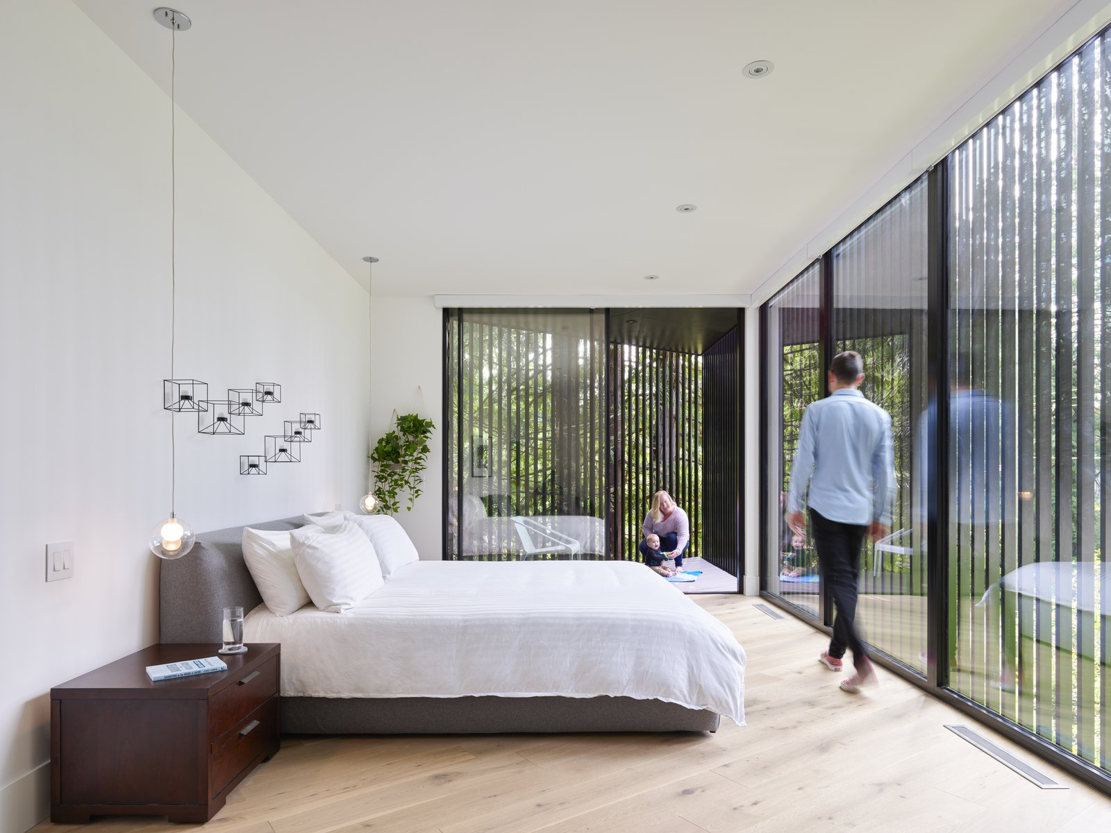 The master bedroom retains a feeling of privacy despite looking out at the street, thanks to a series of slatted wood screens over the floor-to-ceiling glass. The bedroom cantilevers over a ravine to include a small private outdoor deck.