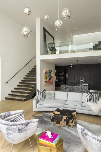 The great room is situated on a lower floor, down the cantilevered staircase from the foyer, with a Nicoline Italia sofa and a variety of textures and patterns enlivening the minimally designed space.