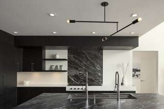 Black marble countertops and backsplash create a high-contrast look in the kitchen.