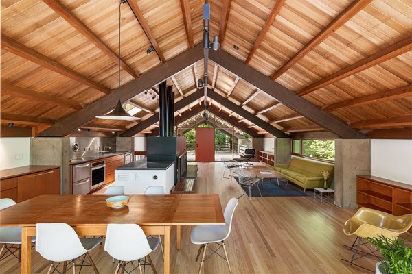 The house's second floor, where one enters, combines the living, kitchen, and dining areas in one space beneath original architect Richard Campbell's vaulted wood ceiling.