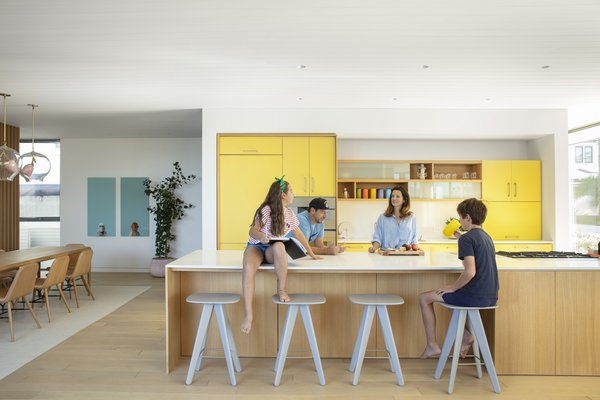 The home's HenryBuilt kitchen is a focal point. The yellow hues of its cabinetry are softened by white oak finishes on the floors and the kitchen island.