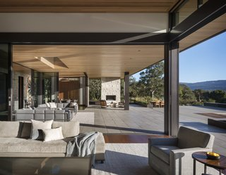 Glass walls in the living room and dining area fold away, connecting to a covered, outdoor space.