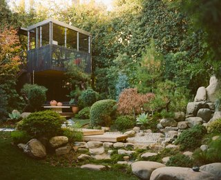 A tea house in the corner of the yard looks out on a small waterfall and pond.