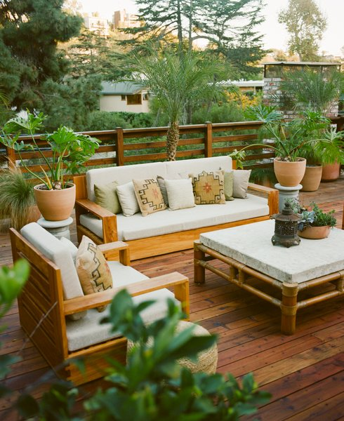A Mission-style sofa and matching club chair are paired with a bamboo-and-stone table on a secondary outdoor deck, where grilling with friends is a popular pastime.