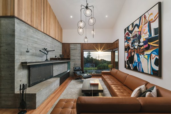 The living room is anchored by a large concrete fireplace that also forms the house's robust structural system. Pops of color come from a painting by Milton Wilson.