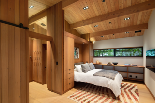 A Murphy bed in one bedroom folds seamlessly into the wall, leaving the rhythm of redwood panels uninterrupted.