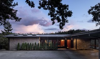 The three-story home, which keeps a low profile at its entrance before sloping downward, is clad in basalt quarried from the site itself.