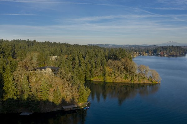 The home is perched on an outcropping above Oswego Lake, with its own boat dock at the bottom of the property.