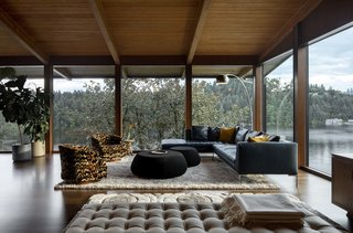 In the living room, the hemlock ceiling extends beyond the full-height glass walls, but not so far as to obstruct the panoramic views.