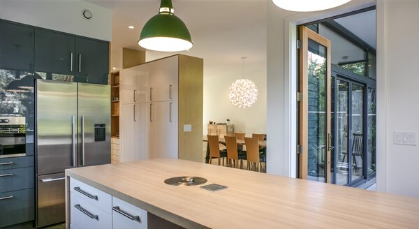 In the kitchen, where fresh air flows continuously in Oregon's mild climate, Ikea cabinetry helped keep costs  down, while the same maple surface was used for an island and flooring to achieve visual clarity.