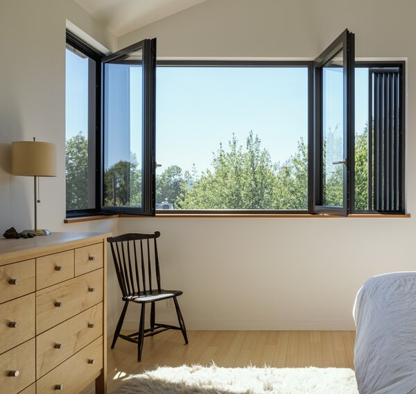 Glo European thermally broken aluminum dual-pane windows, shown here in the master bedroom, give the couple a corner view over the treetops without compromising the building envelope, and can be opened in a variety of configurations.