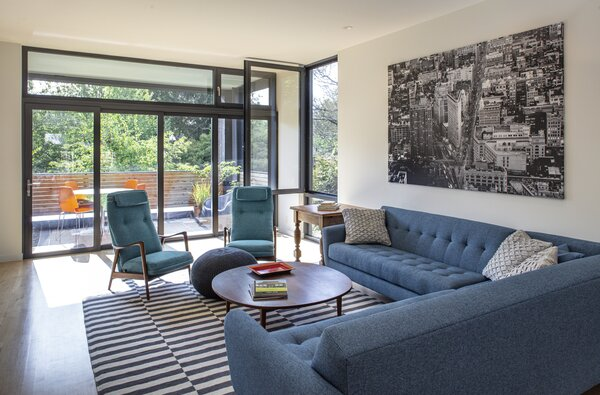 A pair of vintage Ingmar Relling chairs anchor a living room that can take on an indoor-outdoor feel once its moveable wall of front-balcony glass is opened.