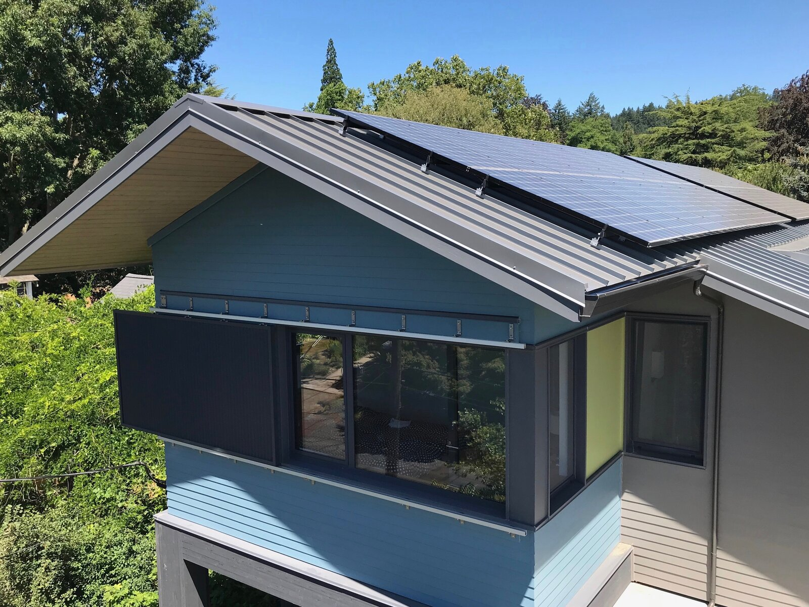 A sliding exterior screen helps keep the master bedroom cool, while the design cuts into the facade to create more corners and windows for better light. Rooftop photovoltaic panels provide all of the home's energy needs.  Photo 8 of 9 in Budget Breakdown: An Architect Couple Build a Net-Zero Home and Studio for $250 Per Square Foot