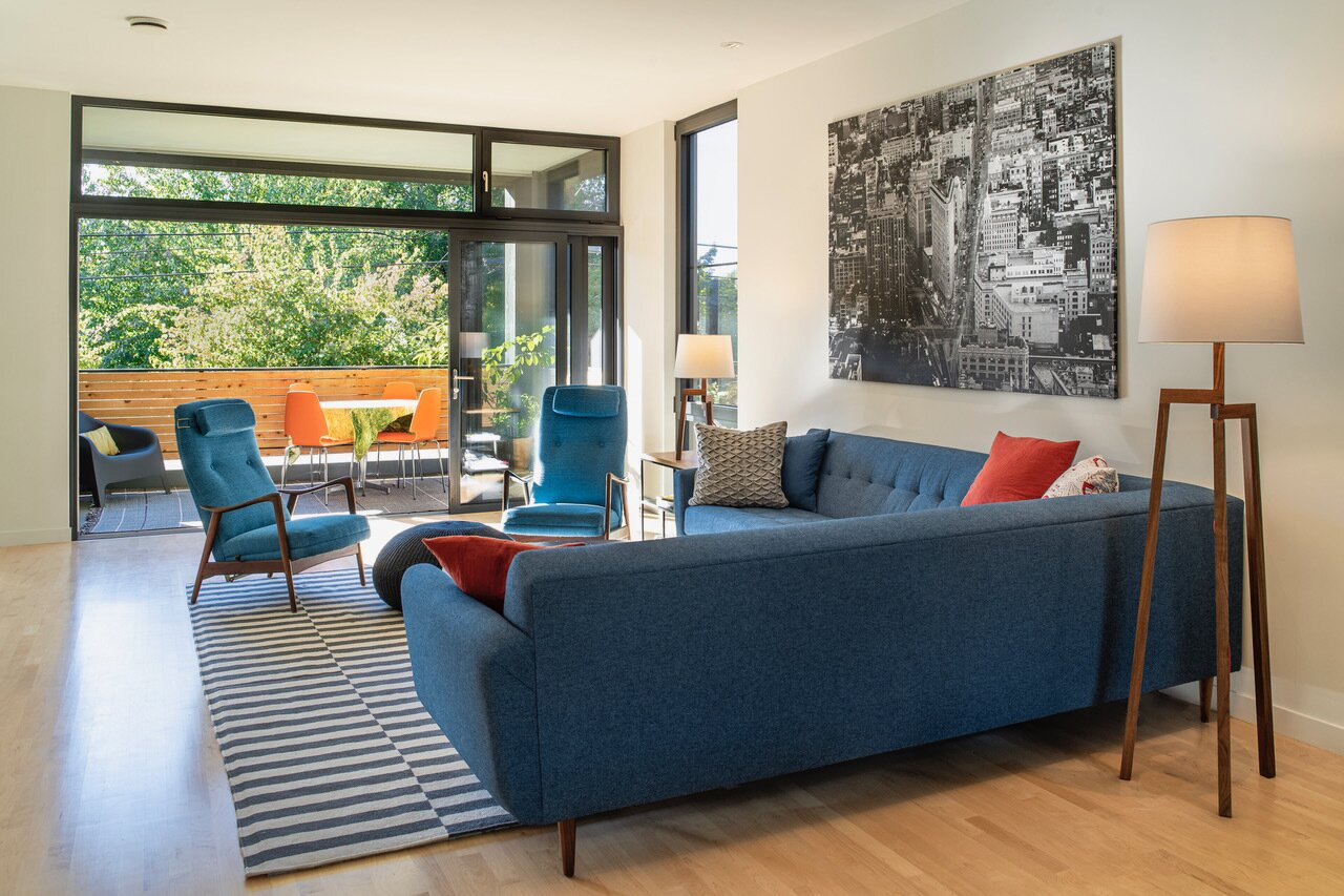 A pair of vintage Ingmar Relling chairs anchor a living room that can take on an indoor/outdoor feel once its moveable wall of front-balcony glass is opened.  Photo 6 of 9 in Budget Breakdown: An Architect Couple Build a Net-Zero Home and Studio for $250 Per Square Foot