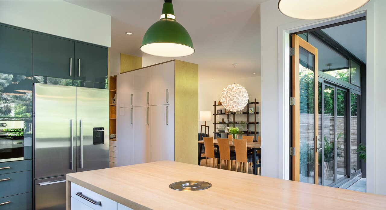 In the kitchen, where fresh air flows continuously in Oregon's mild climate, IKEA cabinetry helped keep costs  down, while the same maple surface was used for an island and flooring to achieve visual clarity.  Photo 2 of 9 in Budget Breakdown: An Architect Couple Build a Net-Zero Home and Studio for $250 Per Square Foot
