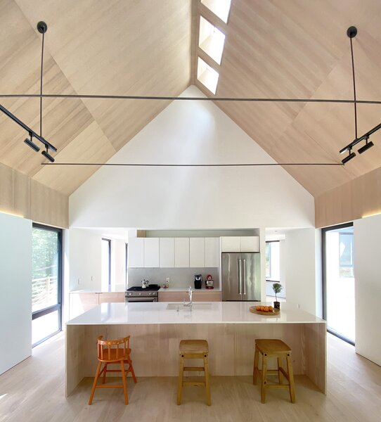 A vaulted ceiling interspersed with skylights, in tandem with floor-to-ceiling glass, fills the home with natural light.