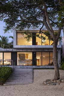 The Hansen Residence—also known as Modern Surf Shack or Casa Los Arboles—is a simple concrete construction, providing a robust envelope to withstand storms (the walls are double the thickness required by code). From the beach, stairs lead up to the main bedroom.