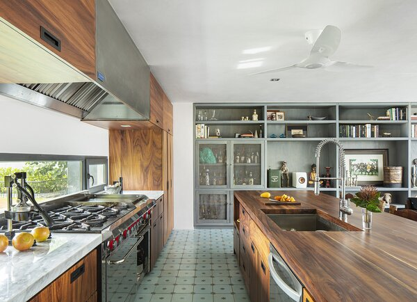 """Parota wood continues in the spacious kitchen. Marisa and Christopher found the blue tile that runs throughout the home on a trip to León, Mexico. """"It called out to us,"""" says Christopher. Festooned with small stars, its tone matches the color of the ocean perfectly."""