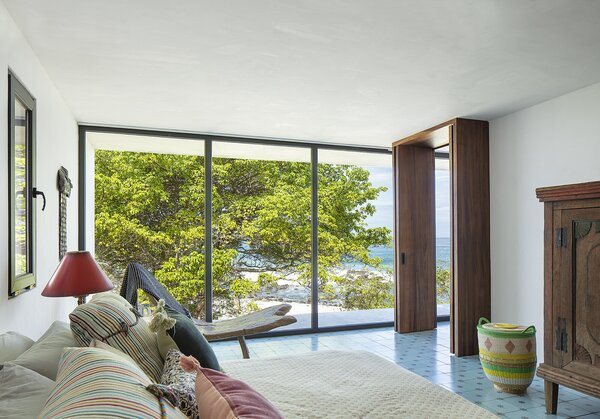 The primary bedroom on the ground floor shows off the couple's antique Indonesian furniture and enjoys a view to the beach through a native amate tree.
