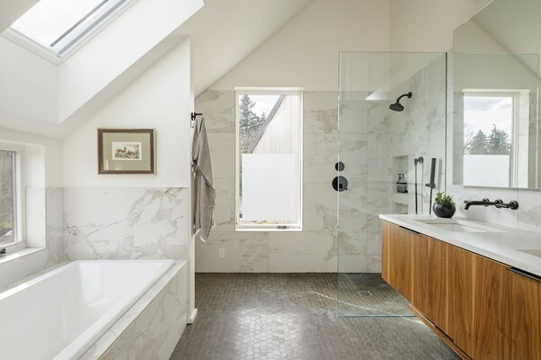 The upstairs master bathroom is teeming with light thanks to its skylight and windows, and looks more luxurious than it is thanks to marble-like ceramic tile and walnut-faced plywood cabinets.