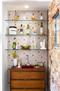 The home's bar features a vintage sink that the homeowners combined with a vintage dresser. Geometric Heath Ceramics for Hygge and West wallpaper serves as a backdrop.
