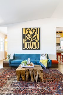 In the living room, a vintage tapestry by Alexander Girard anchors the space. The sofa was found on Craigslist, and the rug was purchased from Blue Parakeet Rugs.