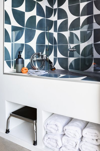 A dog-washing basin near the laundry room, with walls covered in Cle Tile, was designed with the homeowners' three pups in mind.