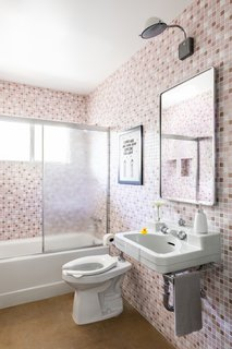 A bathroom for kids features retro-style materials, including a vintage-inspired sink, toilet, and pink mosaic tile.