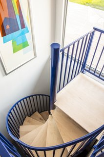 "A spiral stairway leads to the newly constructed basement. ""It's like a piece of playground equipment in the house,"" says Sean Hogan of M Studio Architecture."